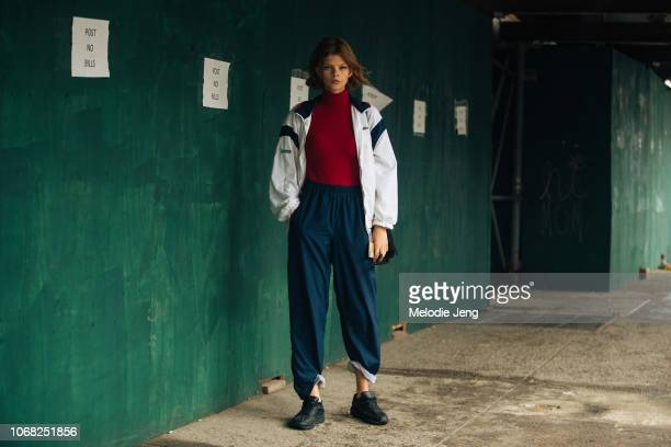 Model Nelly Vakulenko wears a white Lacoste windbreaker red turtleneck blue pants and black sneakers after the Zimmermann show during New York...