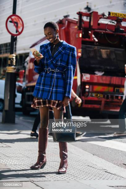 Model Nicole Atieno in a blue plaid blazer and brown boots on the phone during London Fashion Week September 2018 on September 13 2018 in London...