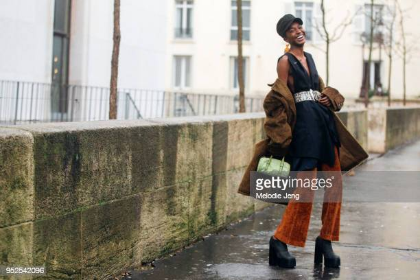 Model Nicole Atieno laughs and wears a black cap brown fur coat off her shoulders sleeveless black top with a belt brown velvet pants and black boots...