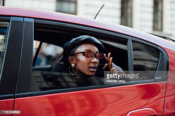 Model Nicole Atieno poses in her car in a black leather beret red skinny sunglasses and hoop earrings after the Halpern show during London Fashion...