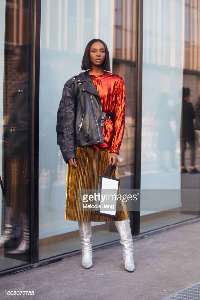 Model Nicole Atieno wears a black leather jacket on one shoulder, a red/orange metallic top with a studded belt, a gold pleated skirt, and silver...