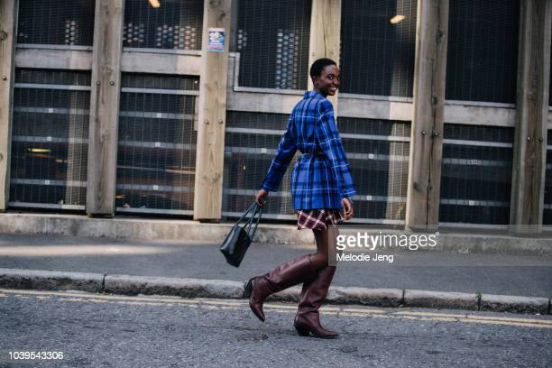 Model Nicole Atieno wears a blue plaid blazer and brown boots after Christopher Kane during London Fashion Week September 2018 on September 13 2018...