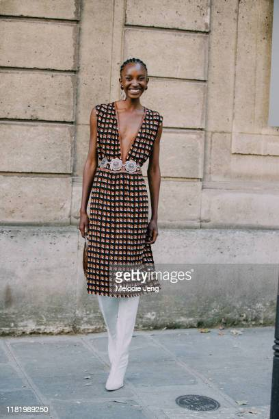 Model Nicole Atieno wears a vintage orange and black print dress with a chunky belt and white boots after the Valentino show during Couture Fashion...