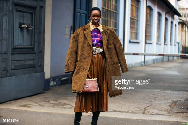 Model Nicole Atieno wears a vintage style purple tattersall top, a python leather belt, brown pleated leather skirt, brown purse, and black boots...