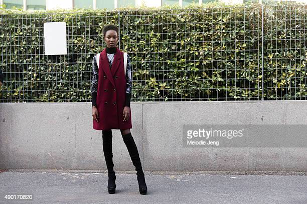 Model Nicole Atieno wears a wool maroon jacket vest with thighhigh boots during the Milan Fashion Week Spring/Summer 16 on September 26 2015 in Milan...
