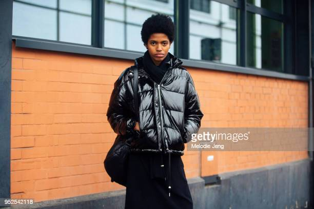 Model Nicole Mateo wears a black reflective jacket backpack scarf and dress after the Balenciaga show on March 04 2018 in Paris France