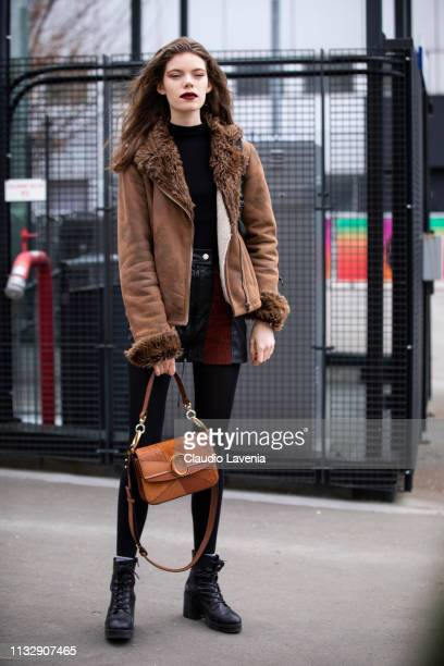 Model Nina Gulien wearing a black top brown jacket black and red mini skirt black boots and tan Chloe bag is seen outside Chloe on Day 4 Paris...