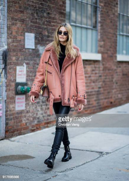 Model Noel Berry wearing salmon colored shearling jacket seen outside Zadig Voltaire on February 12 2018 in New York City