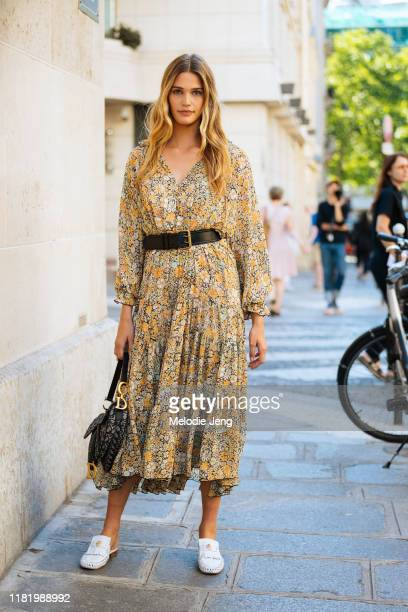 Model Noel Berry wears a yellow floral dress with a belt, Christian Dior saddle bag, and white Versace loafers after the Zuhair Murad show during...