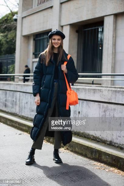 Model Noor Chaltin wears a black beret, black sleeping bag style down coat, and orange purse after the Miu Miu show during Paris Fashion Week...
