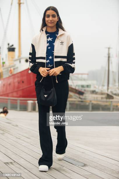 Model Nora Attal wears a pink Adidas track jacket blue star sweater black Prada bag black pants after the Michael Kors show during New York Fashion...