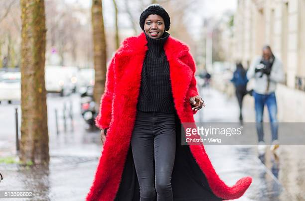 Model Nykhor Paul wearing a red fur coat black denim jeans and a black turleneck outside Rochas during the Paris Fashion Week Womenswear Fall/Winter...