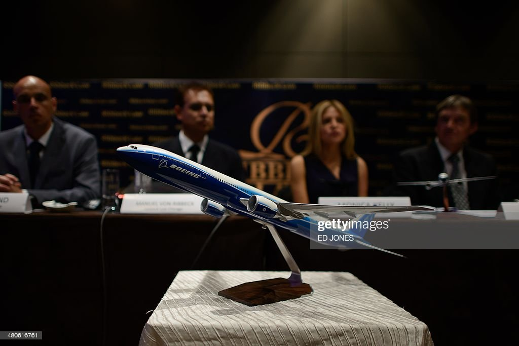 A model of a Boeing 777 aircraft is displayed as representatives of US law firm Ribbeck Law Chartered International hold a media briefing at a hotel in Kuala Lumpur on March 26, 2014. A US law firm said it has started 'multi-million dollar' legal proceedings against Malaysia Airlines and Boeing over flight MH370, in what could mark the start of an expensive legal battle over the lost plane. AFP PHOTO / Ed Jones