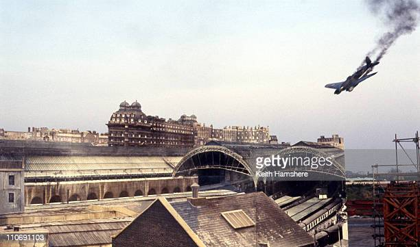 A model of a Heinkel bomber is guided onto a photographic cutout of Victoria Station during filming for 'Battle Of Britain' directed by Guy Hamilton...