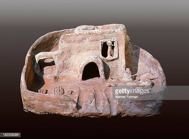 A model of a house with a rounded door and a staircase to the roof which has a vent to catch the cool breeze Funerary models like these which...