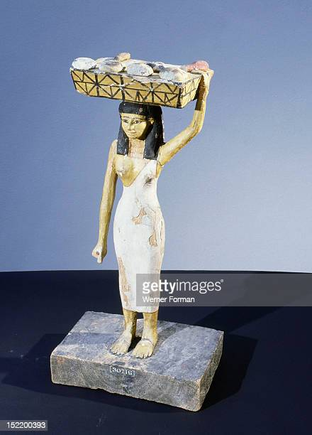 A model of a servant girl carrying on her head a basket of loaves and pieces of meat Egypt Ancient Egyptian Middle Kingdom