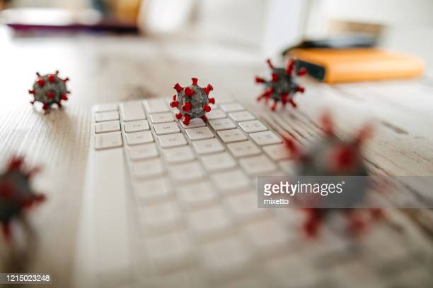 model of corona virus on desk and keyboard in office - computer keyboard stock pictures, royalty-free photos & images