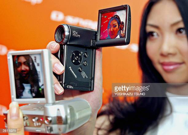 A model of Japan's electronics giant Matsushita Electric Industrial displays the new digital video camera series Dsnap to record on the stamp sized...
