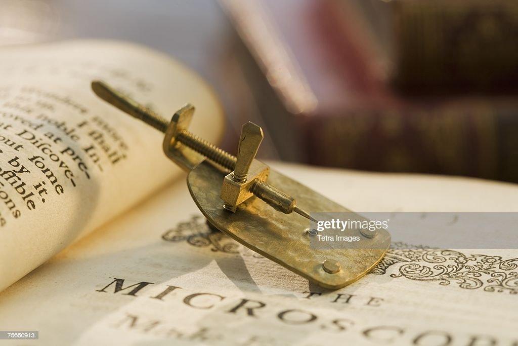 Model of Leeuwenhoek microscope on book : Stock Photo