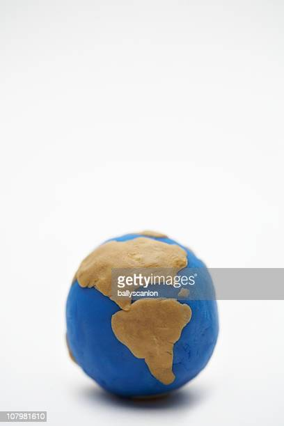 Model of planet earth made on clay on white backgr