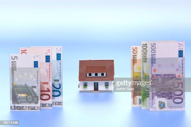 model of residential house with european currency in foregroud, close-up - five euro banknote stock photos and pictures