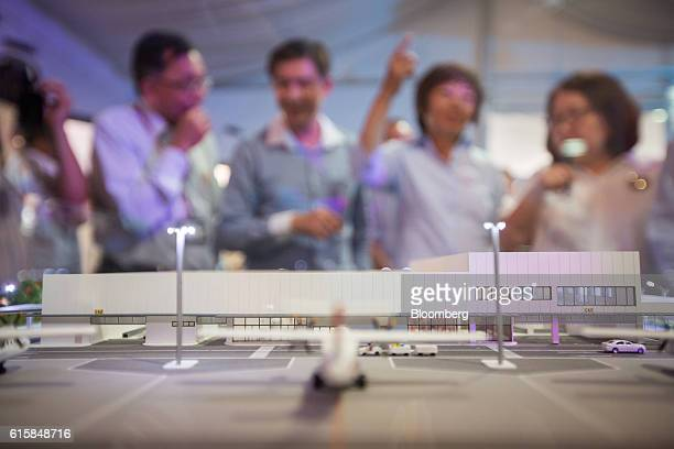 A model of Seletar Airport's new passenger terminal sits on display as journalists look on during a groundbreaking ceremony in Singapore on Thursday...
