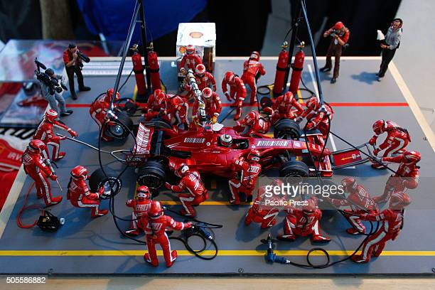 A model of the moment at the Pit Stop Ferrari in Formula One with men pulling it while press capturing photos of it during modeling exhibition at...