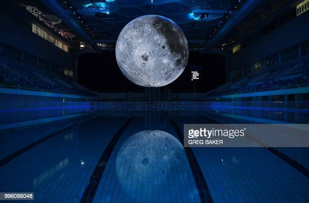 TOPSHOT A model of the moon hangs above the Olympic swimming pool at the National Aquatics Center known as the Water Cube in Beijing on July 11 2018...