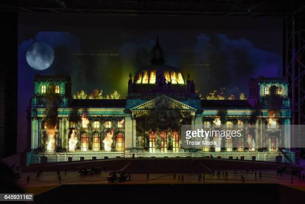 A model of the Reichstag is overlayed with an animated video of flames and smoke as model figures look on in a representation of the Reichstag fire...