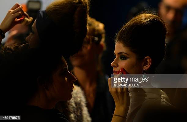 A model of the Spanish designer Francis Montesinos is madeup before the Autumn/Winter 20142015 collection presentation during Madrid Fashion Week in...
