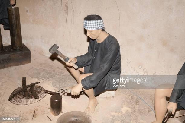 Model of Vietnamese man making weapons at Ben Dinh Cu Chi near Ho Chi Minh City Vietnam