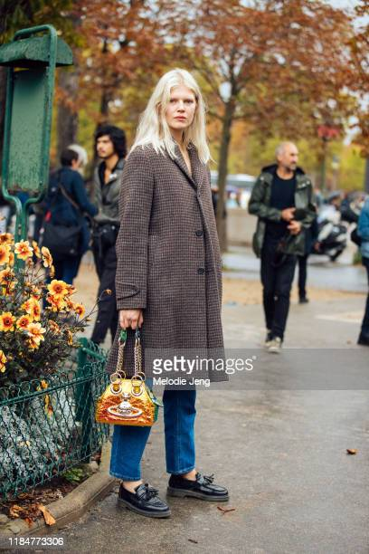 Model Ola Rudnicka wears a dark houndstooth coat, gold purse, blue jeans, and black leather loafers after the Chanel show during Paris Fashion Week...