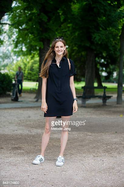 Model Olivia Jansing wears a blue shirt dress and white Adidas superstar sneakers at Jardin du Luxembourg June 25 2016 in Paris France