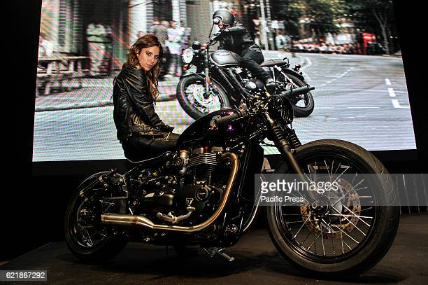 A model on a Triumph Bonneville Bobber motorbike poses for the visitors during the 74th EICMA International Motorcycle Exhibition