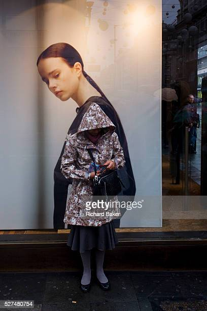 Model on an Adidas seemingly looks over her shoulder to watch a woman checking her bag on Oxford Street London Wearing a raincoat and hood pulled...