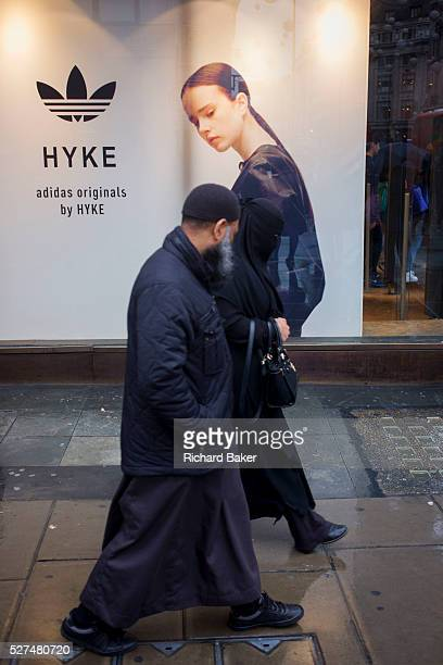 Model on an Adidas seemingly looks over her shoulder to watch muslim passersby on Oxford Street London The middleaged couple are walking along the...