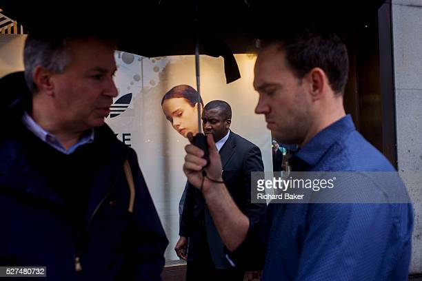Model on an Adidas seemingly looks over her shoulder to watch passersby on Oxford Street London As two men hold a conversation under an umbrella in...