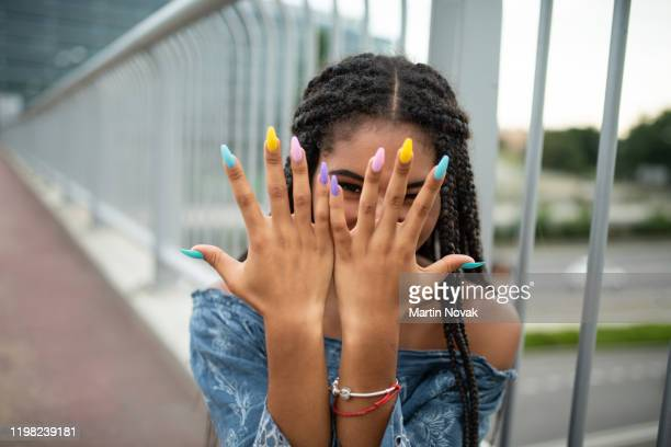 model on city bridge posing with colorful nails - nail polish stock pictures, royalty-free photos & images