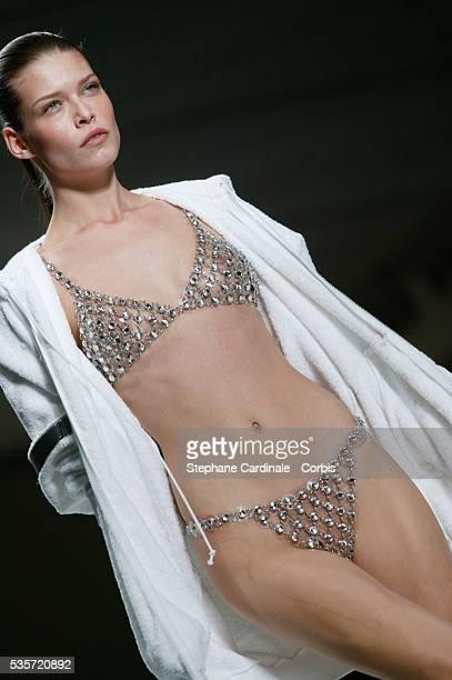 Model on the catwalk wearing a chainmail style bikini and bathrobe