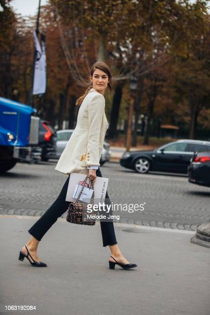 Model Ophelie Guillermand attends the Chanel show in a white tweed blazer, red and black Chanel bag, black cropped pants, and black slingback pump...