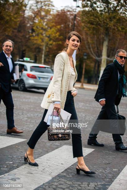 Model Ophelie Guillermand attends the Chanel show in a white tweed blazer red and black Chanel bag black cropped pants and black slingback pump shoes...