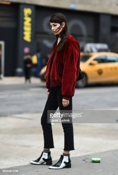 Model Ophelie Guillermand is seen wearing a red jacket black pants white sweater black and white shoes and teal eye liner outside of the ROCHAMBEAU...