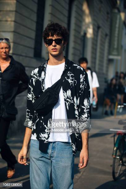 Model Oscar Kindelan wears a Prada crossbody bag floral black shirt white shirt blue jeans and black RayBan sunglasses during Milan Fashion Week...
