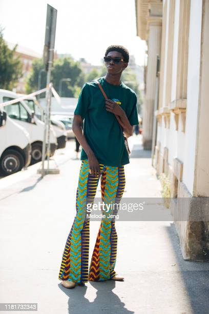 Model Ottawa Kwami wears a green Daily Paper shirt and multi-print and color flared African-style pants after the Fendi show during the Milan Men's...