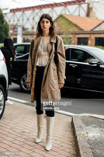 Model Oyku Bastas wears a tan Burberry trench lace cream top black pants and white Dorateymur kneehigh boots after the Gucci show during Milan...