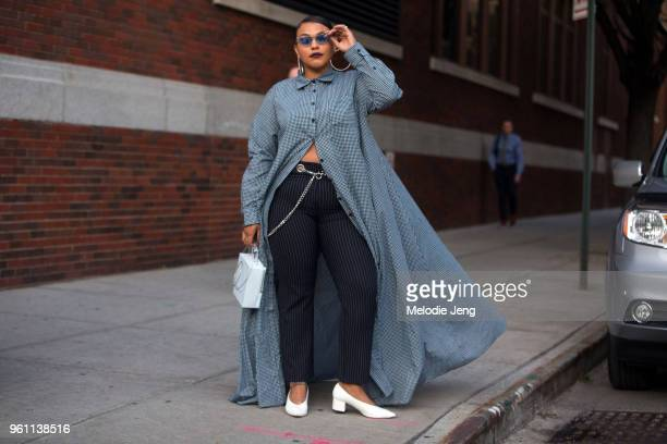 Model Paloma Elsesser wears a long green dress shirt and black striped pants with white low heels and triangular futuristic sunglasses during New...