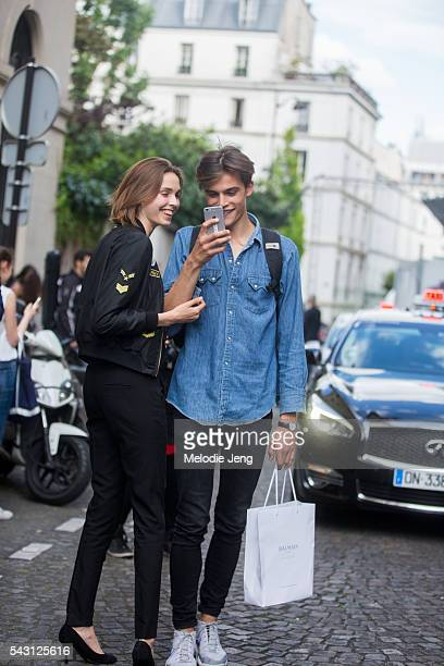 Model Parker Van Noord wears a chambray shirt and takes a photo on his iphone and a guest wears a black US Army bomber jacket black jeans and black...