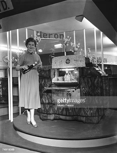 Model Pat Manwaring with the Marilyn De Luxe cocktail cabinet in a walnut veneer finish at the British Furniture Exhibition at Earl's Court, London,...
