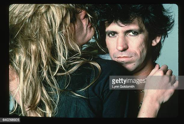 Model Patti Hansen embraces her husband Keith Richards guitarist for the British rock roll band The Rolling Stones She has her back turned to the...