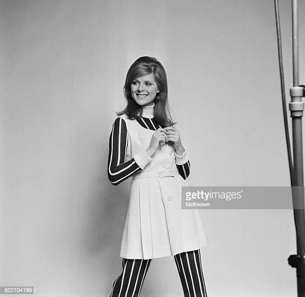 Model Paulene Stone wearing a pleated wool pinafore dress over a striped knitted jumpsuit 4th March 1969